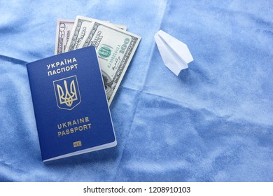 Ukrainian biometric passport and dollars. Paper plane and international passport on blue background. Money and documents for trip abroad. Migration documents