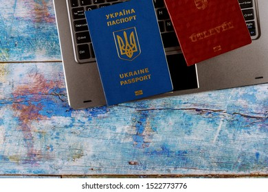 Ukrainian biometric passport and Hungarian passport in dual citizenship with computer keyboard filling in document applying for registering