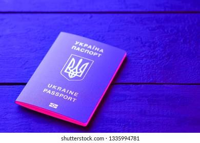 Ukrainian biometric passport on dark background. Ukrainian international passport on black boards, top view. Document for traveling abroad in blue light
