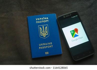 Ukrainian biometric passport and smartphone with an open Google map application.
