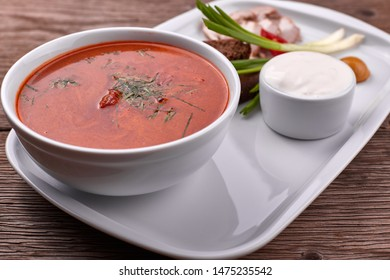 Ukrainian borsch with sour cream, onions and bacon on a white plate