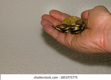 Ukrainian coins in a man's hand. Ukrainian pennies on a white background close-up. Coins in a heap close-up, in the form of a falling pyramid, in a man's hand