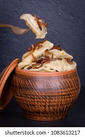 Ukrainian dishes - vareniki or dumplings with mashed potatoes or cottage cheese in clay pot on a black slate background, fork and dumpling, close up