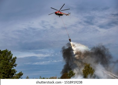 Ukrainian firefighting helicopter dropping a load of water to extinguish the fire in the forest. Training of rescue services near Kyiv, Ukraine. September 2019.