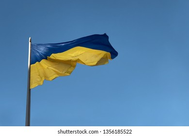 Ukrainian flag fluttering in the wind against a blue sky. presidential elections in Ukraine 2019. Blue and yellow Ukrainian national flag on a flagpole against a blue cloudy sky, copy space for text