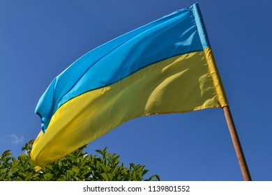 Ukrainian Flag in front of a clear blue sky.