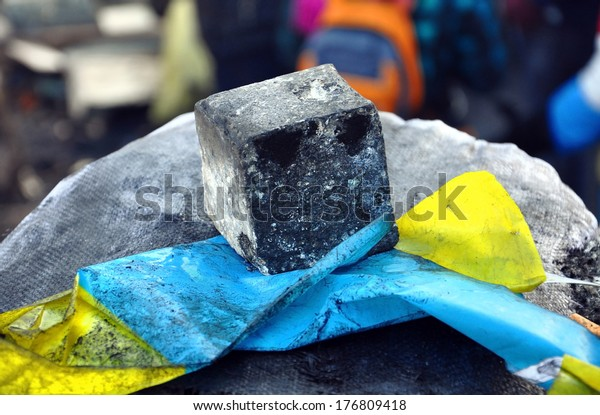 Ukrainian flag pressed to a stone with a piece of cobbles