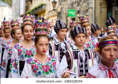 Ukrainian Folklore group of kids in local costume walking down streets of Lviv during opening the Parade of Etnovyr Festival in street of Lviv. Lviv, Ukraine - August 22, 2019