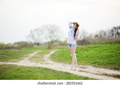 Ukrainian girl in a shirt and a flower wreath on his head on a background of green grass