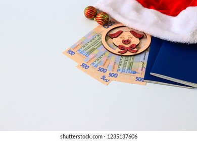 Ukrainian hryvna, 500 hryvnia,  red Santa Claus hat, blue passport, pig on a light, wooden background. Christmas, New Year, travel, tourism concept. Ukraine. gryvnia, gryvna, grivna, grivnia, hrivnia