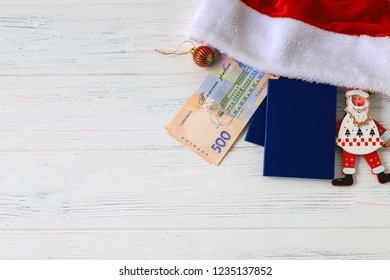 Ukrainian hryvna, banknotes 500 hryvnia, with red Santa Claus hat and blue passport on an old light, wooden background. Christmas, New Year and travel  concept, Travel and tourism.  Ukraine