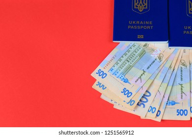 Ukrainian hryvna, banknotes 500 hryvnia, with blue passport on red background. Christmas, New Year, tourism, and travel  concept.  Ukraine