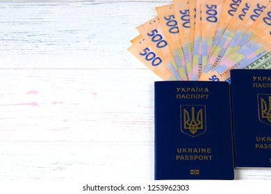 Ukrainian hryvna, banknotes 500 hryvnia, with blue passport on an  light, wooden background. Christmas, New Year, tourism,  and travel  concept.  Ukraine