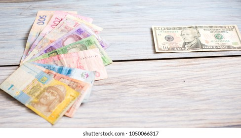 Ukrainian hryvnia and American dollars on a wooden background