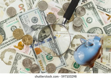 Ukrainian hryvnia and American's dollars with a piggy bank and magnifying glass, soft focus background