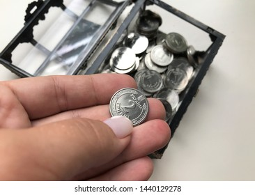 Ukrainian hryvnia. Ukrainian currency. Cash savings, one and two hryvnia coins, little chest with a trifle, woman's hand puts two hryvnia coin. Close-up.