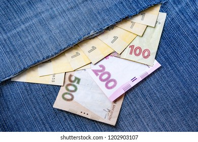 Ukrainian hryvnia falls out of a torn denim pocket. 100, 200 and 500 hryvnia bills sticking out of denim. Paper notes. Losing money from your pocket. Business concept.