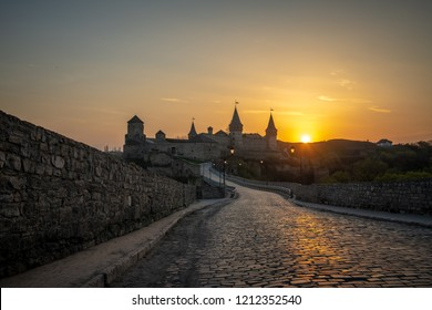 Ukrainian Kamianets-Podilskyi fortress at sunset with beautiful view, city and cobblestone road