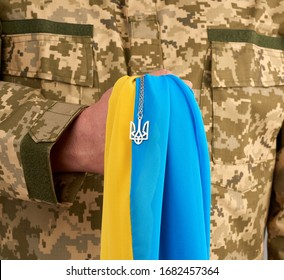 Ukrainian man warrior dressed in a military pixel uniform holds the yellow-blue flag of the state of Ukraine and on the chain a small coat of arms of the country of trident, close up