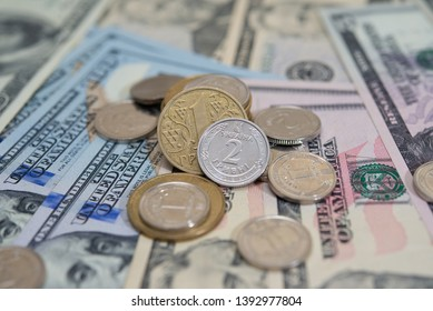 Ukrainian metal coins of 1, 2 hryvnias stacked against 5, 50, 100 American dollars, the concept of confrontation, reduction of the hryvnias and the dollar, strengthening of the hryvnias, selective foc