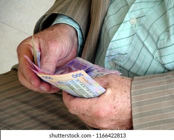 Ukrainian money (hryvnia) in the hands of old man