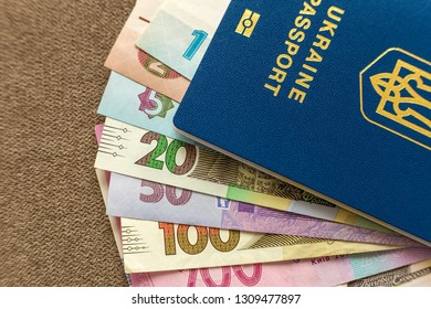 Ukrainian passport and money, Ukrainian hryvna banknotes bills on copy space background, top view. Traveling and  finance problems concept.
