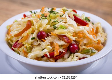 Ukrainian and Russian dishes - homemade marinated, sour cabbage with carrots and onions in a white plate on the wooden table, close up