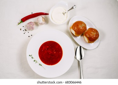 Ukrainian and Russian traditional beet soup - borscht in a white plate with sour cream, spices, garlic, red pepper, dried herbs and pampushkas on a white dish, healthy food.