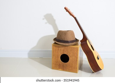 Ukulele and brown hat on cajon with white wall background