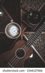 Ukulele, Coffee grinder and Coffee cup, on table. Music instrumentation concept. soft focus,motionblur