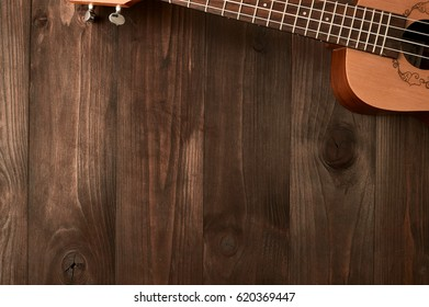 Ukulele lies on a wooden background. Top view. Free space