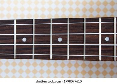 Ukulele neck. Guitar strings and frets