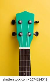 Ukulele neck on a yellow background. Ukulele details close-up. Ukulele guitar.