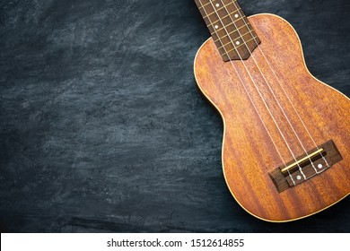 Ukulele on black cement background. Body and bridge of ukulele parts. Copy space for text. Concept of summer ukulele or Hawaiian musical instruments.