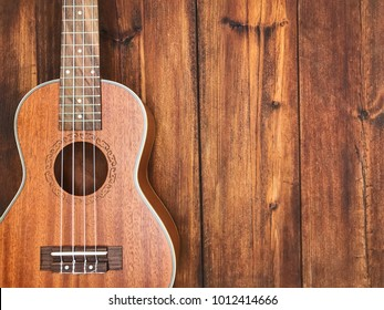 A ukulele on brown wooden background.