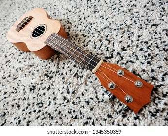 Ukulele on carpet in the living room, shallow depth of field