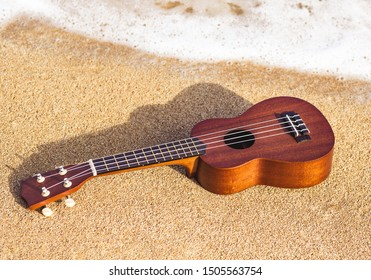 Ukulele on the sandy beach in Hawaii.