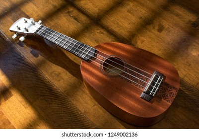 A ukulele on a wooden background with sunlight and hard shadows and warm feel.