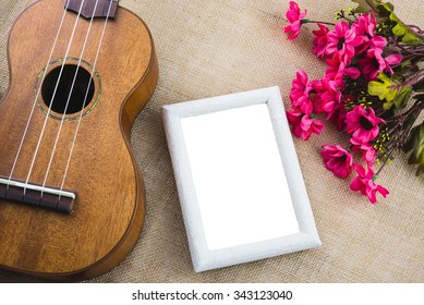 Ukulele and picture frame on sackcloth