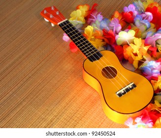 Ukulele surrounded by Hawaiian style leis cast in golden sunlight.