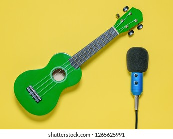Ukulele ukulele ukulele and wired blue microphone on yellow background. The view from the top.