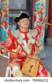 ULAANBAATAR, MONGOLIA - AUGUST 16, 2006: Unidentified man wearing traditional costume performs music with morin khuur - national musical instrument in Ulaanbaatar, Mongolia.