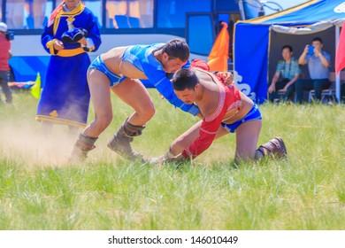 "ULAANBAATAR, MONGOLIA - JULY 4: The Mongolian wrestlers wrestling in the field , Ulaanbaatar on July 4, 13,  Wrestling is the most important of the Mongolian culture's historic ""Three Manly Skills"""