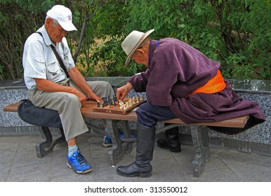 ULAANBAATAR, MONGOLIA - JULY 8, 2015: two old men are playing chess in park of Ulaanbatar, Mongolia