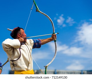 Ulaanbaatar, Mongolia - June 11, 2007: A traditionally dressed man archer taking aim with his bow and arrow at the Naadam Festival archery competition