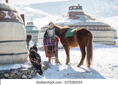 ULAANBAATAR, MONGOLIA - MARCH 5 2018 : young mongolian girl setup her horse in the morning for join the Golden Eagle Festival.