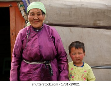 Ulaanbaatar / Mongolia - May 29, 2001: An old Mongolian Grandmother stands with her young Granddaughter outside their yurt near UlaanBaatar, Mongolia.