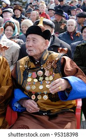 ULAN-UDE, RUSSIA - MAY 9: An elderly veteran in Buryat national clothes wearing a lot of decorations watches the parade on annual Victory Day, May, 9, 2009 in Ulan-Ude, Russia.