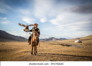 ULGII, MONGOLIA - CIRCA OCTOBER, 2015: Mongolian Eagle hunter in traditional clothing, holding a golden eagle on his arm and sitting on his horse with a yurt at the background.