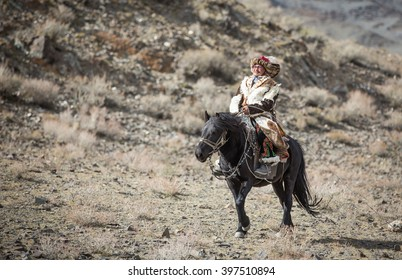 ULGII, MONGOLIA - CIRCA OCTOBER 2015: man, dressed in traditional Kazakh outfit is riding a black horse